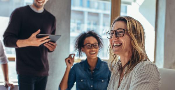 Femme souriante au travail avec des collègues - marque employeur