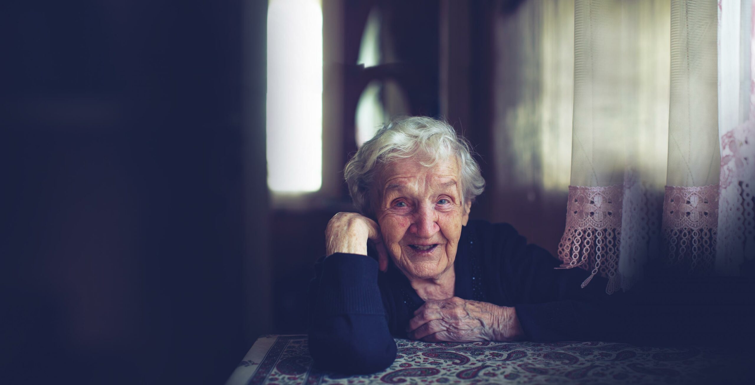 Smiling elderly woman sitting at a table